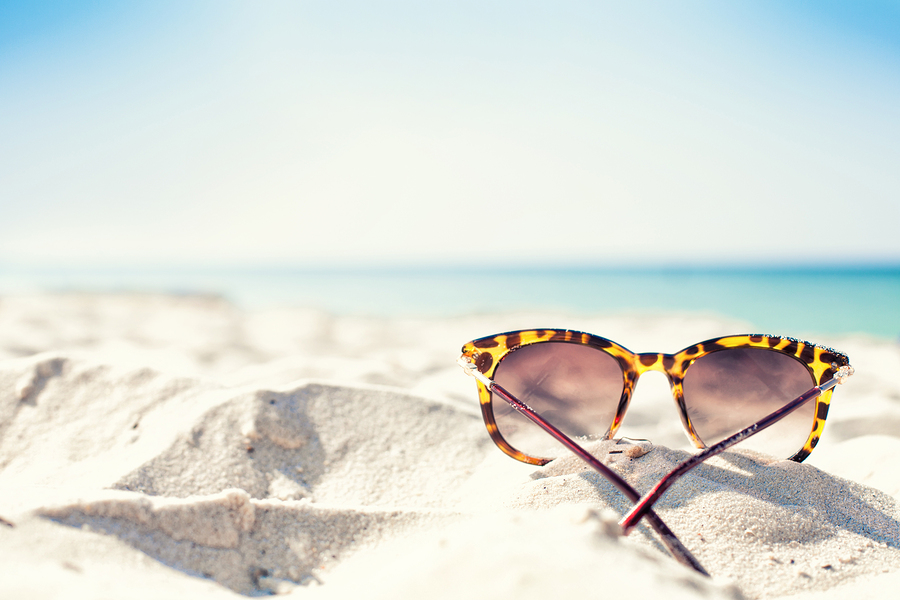 Sun glasses lie on a beach near the sea ** Note: Shallow depth of field